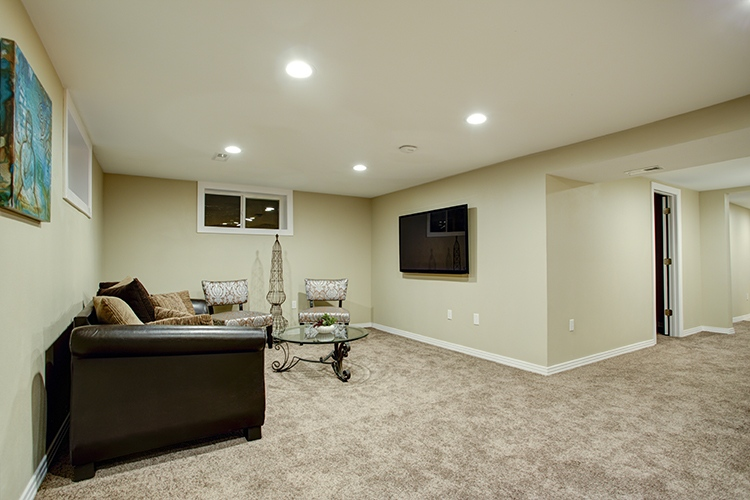 Stunning basement interior with cozy atmosphere, furnished with leather sofa, glass top cocktail table and soft carpet floor.