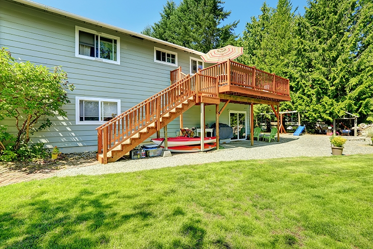 Countryside house with wooden walkout deck and patio area