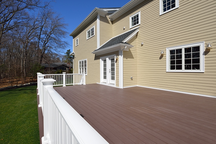 Large new deck in house backyard. Composite boards, white railing posts and veranda