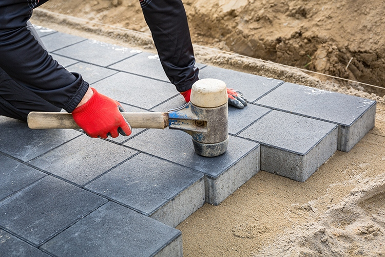 Hands of worker installing concrete paver blocks with rubber hammer